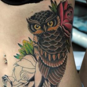 Татуировка на боку у девушки - сова и цветы