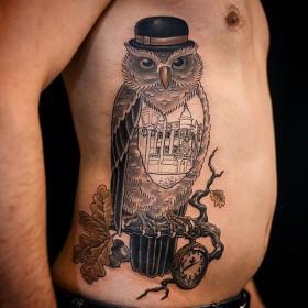Татуировка на боку у парня - сова