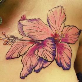 Татуировка на груди у девушки - лилии