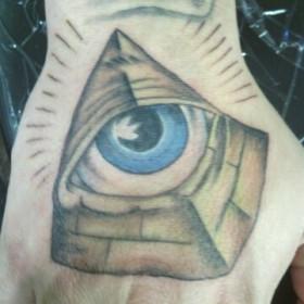 Татуировка на кисти парня - пирамида с глазом
