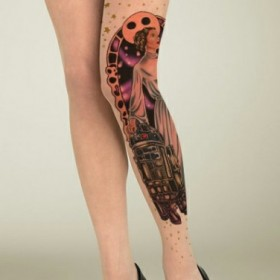 Татуировка на ногах у девушки в виде колготок с рисунком в виде девушки