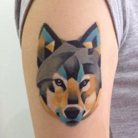 Татуировка на плече у девушки - волк