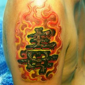 Татуировка на плече у парня - иероглифы в огне