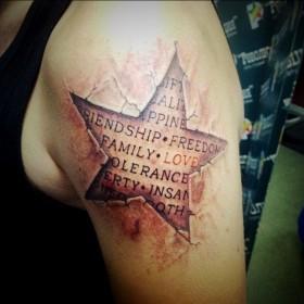 Татуировка на плече у парня - звезда с надписью на английском