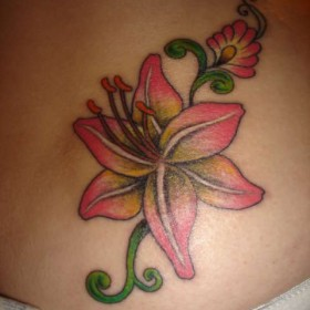 Татуировка на пояснице у девушки - лилия