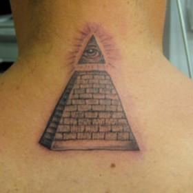 Татуировка на позвоночнике парня - пирамида с глазом