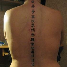 Татуировка на позвоночнике у девушки - иероглифы