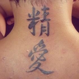 Татуировка на позвоночнике у парня - иероглифы