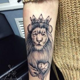 Татуировка на предплечье у девушки - лев с короной