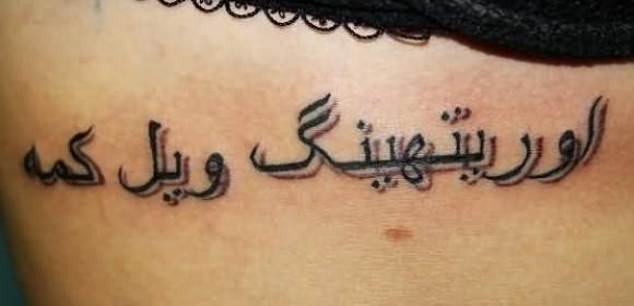 Татуировка на ребрах девушки - надпись на арабском