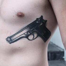 Татуировка на ребрах у парня - пистолет