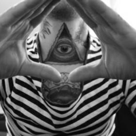 Татуировка на шее парня - пирамида с глазом