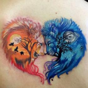 Татуировка на спине девушки - львы