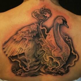 Татуировка на спине у девушки - лебедь