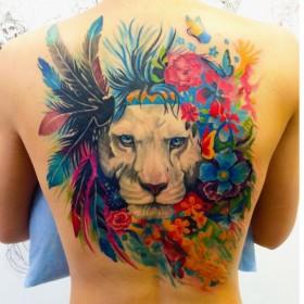 Татуировка на спине у девушки - лев, перья и цветы