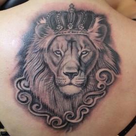 Татуировка на спине у девушки - лев с короной