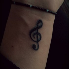 Татуировка на запястье девушки - скрипичный ключ