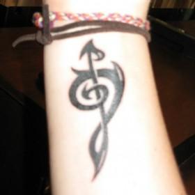 Татуировка на запястье у девушки - скрипичный ключ