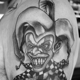 Татуировка шута на плече мужчины