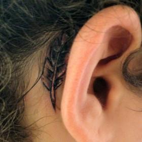 Татуировка в стиле чикано за ухом девушки - перо