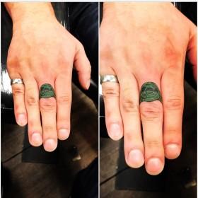 Зеленая татуха кольца на среднем пальце мужчины