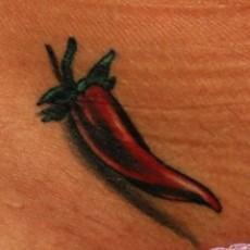 Цветная татуировка на животе девушки - перчик