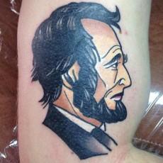 Линкольн - цветная тату на бицепсе парня
