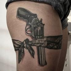 Тату на бедре девушки - пистолет