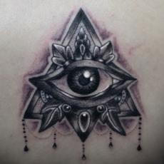 Тату на лопатке девушки - массонский глаз и треугольник