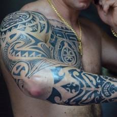 Тату на руке и груди мужчины в стиле полинезия