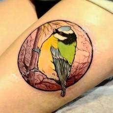 Тату в цвете на бедре девушки - птичка