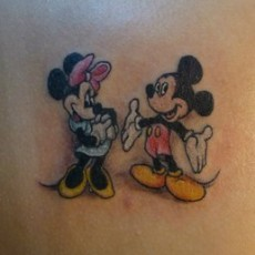 Татуировка на лопатке девушки - Микки и Минни Маус