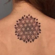Татуировка на позвоночнике девушки - мандала