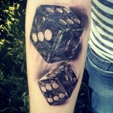 Татуировка на предплечье парня черной тушью - игральные кости