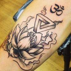 Татуировка на руке парня - ом и лотос