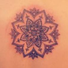 Татуировка на спине девушки - мандала