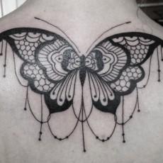 Татуировка на спине у девушки - бабочка