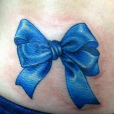 Татуировка на животе у девушки - бантик