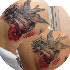 Татуировка в реалистичном стиле на лопатке девушки - ласточка и песочные часы