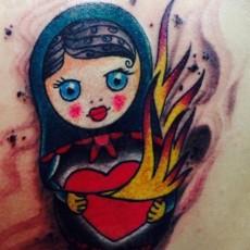 Татуировка в стиле олд скул на бедре девушки - матрешка