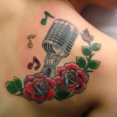Татуировка в стиле олд скул на лопатке девушки - микрофон и розы