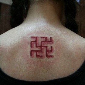 Татуировка амулета одолень-трава на спине девушки